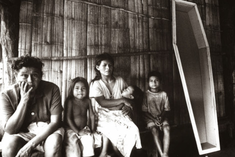 Guarani family from Brazil sit next to a coffin