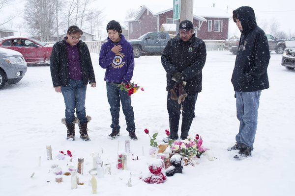 A family in La Loche, Saskatchewan, pay their respects on Saturday, Jan. 23, 2016, to the victims of a Friday school shooting.