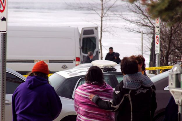 Onlookers gather on Water Street as Kenora detachment OPP investigate a report of human remains located in Lake of the Woods, Tuesday morning, March 22. REG CLAYTON/Miner and News